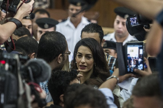 Amal Clooney (C), the human rights lawyer representing Canadian Al-Jazeera journalist Mohamed Fahmy (unseen), talks to the press during the trial of Fahmy and Egyptian Baher Mohamed, both accused of supporting the blacklisted Muslim Brotherhood in their coverage for the Qatari-owned broadcaster, on August 29, 2015, in the capital Cairo. The court sentenced Fahmy and Mohamed, along with Australian journalist Peter Greste who was tried in absentia after his deportation early this year, to three years in prison in a shock ruling following global demands for their acquittal. AFP PHOTO / KHALED DESOUKI (Photo credit should read KHALED DESOUKI/AFP/Getty Images)