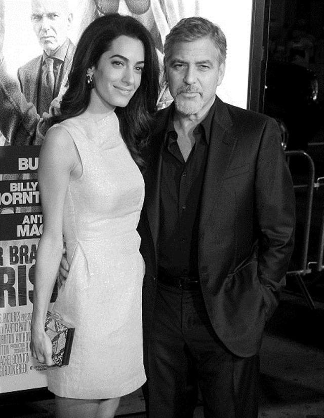 HOLLYWOOD, CA - OCTOBER 26: (EDITORS NOTE: Image has been converted to black and white.) Actor George Clooney and wife Amal Clooney arrive at the premiere of Warner Bros. Pictures'